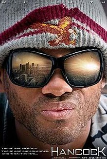"Close portrait of a man with stubble on his face and large sunglasses in which the reflection of a city's landscape, awash in sunlight, can be seen.  The man is wearing a gray knitted cap with a dark red rim; stitched in the front of the cap is a orange-tinted bald eagle with its wings spread.  In the lower right corner of the poster is the name ""HANCOCK""."