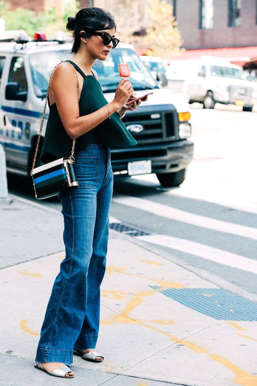 Le Fashion Blog Street Style Sunglasses Black Sleeveless Crop Top Wide Leg Jeans Metallic Sandals Via Vogue Paris