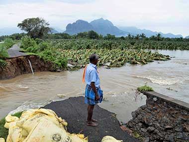 A man watches a road that has been cut off  due to floods caused by the cyclone Ockhi, which caused heavy damage in Kanyakumari. PTI