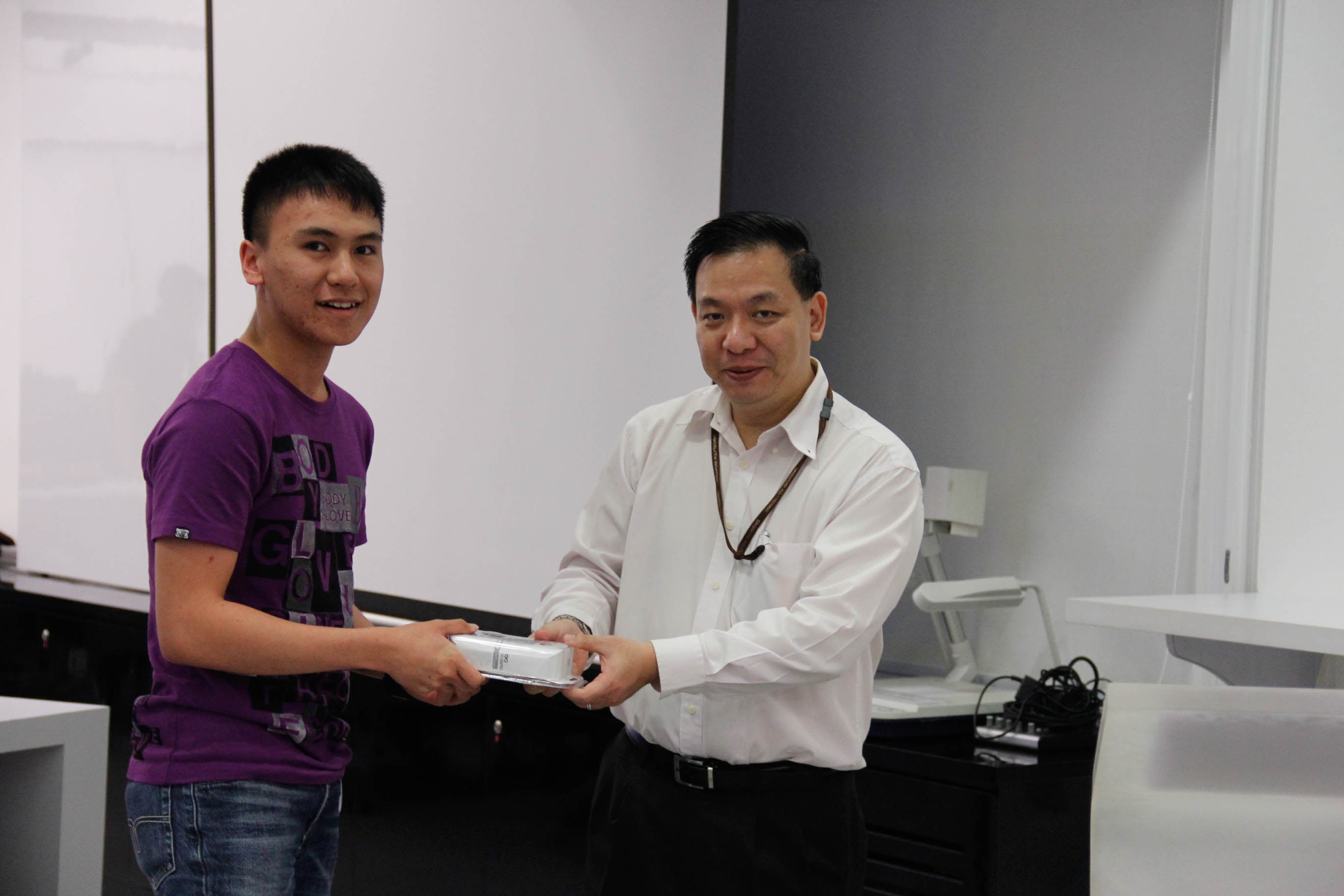 New ISACA Student Member and lucky draw winner Mustaqiim receiving prize from DISM lecturer Mr Samson Yeow