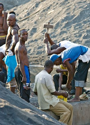 Risky: Locals dig through mountains of mining waste looking for scraps of metal ore in The Congo