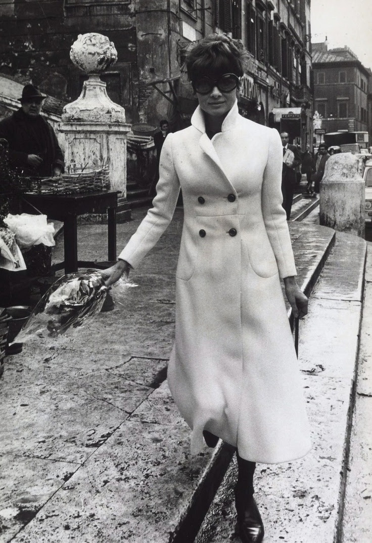 """Signora Audrey Hepburn Dotti photographed atPiazza di Spagnain Rome (Italy), in October 1970.  -Audrey was wearing coat ofValentino(made of white wool, of his collection for the Autumn/Winter 1970/71), sunglasses ofOliver Goldsmith(the same that she wore in """"Charade"""") andCélineshoes."""