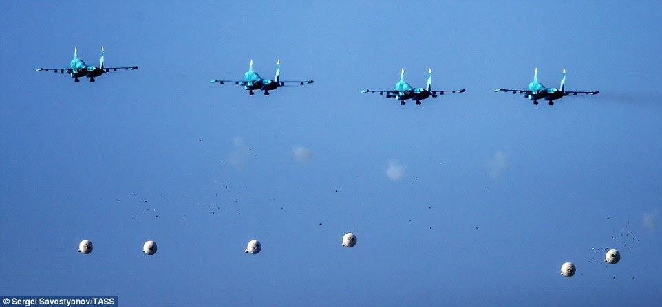 Four blue Sukhoi Su-34 strike fighters release their payloads. The bombs drift down in an almost even line in an impressive display of military timing