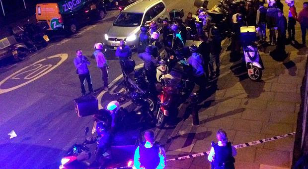 Handout photo taken with permission from the Twitter feed of @sarah_cobbold of Deliveroo and UberEATS drivers at the scene along with police after two men on a moped carried out five acids attacks Photo: @sarah_cobbold/PA Wire