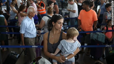 SAN JUAN, PUERTO RICO - SEPTEMBER 26: Noelia Torres and Orlando Liam Bear,1,  on her way to Orlando, Fl and others wait in line to clear through security to catch a flight out of the Luis Munoz Marin International Airport as they try to return home after Hurricane Maria on September 26, 2017 in San Juan, Puerto Rico.  Some of the people have waited days at the airport in hopes of getting onto a plane after Hurricane Maria, a category 4 hurricane, devastated the island.  (Photo by Joe Raedle/Getty Images)