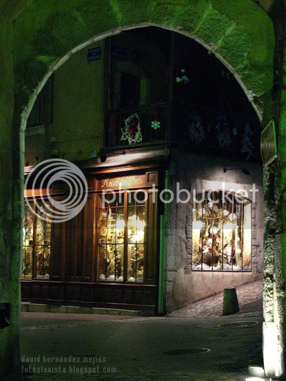 Vista de una calle de Annecy, Francia, de noche a través de un arco de piedra en época navideña