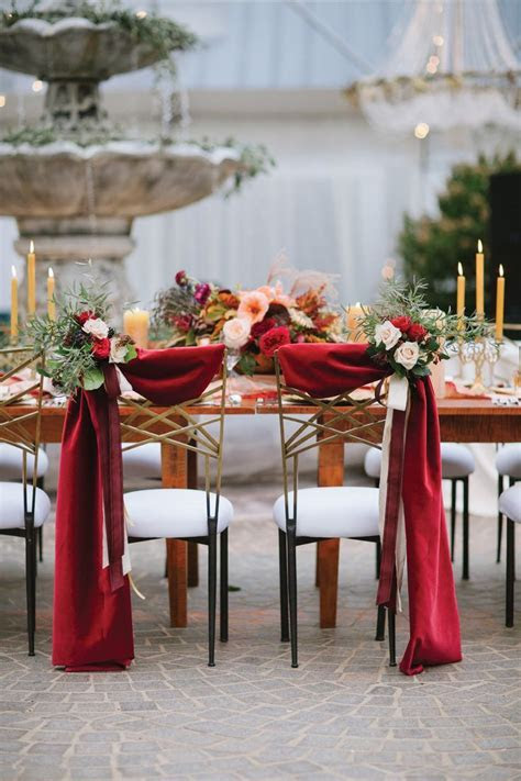 Bride and groom chair decor with scarlet fabric draping