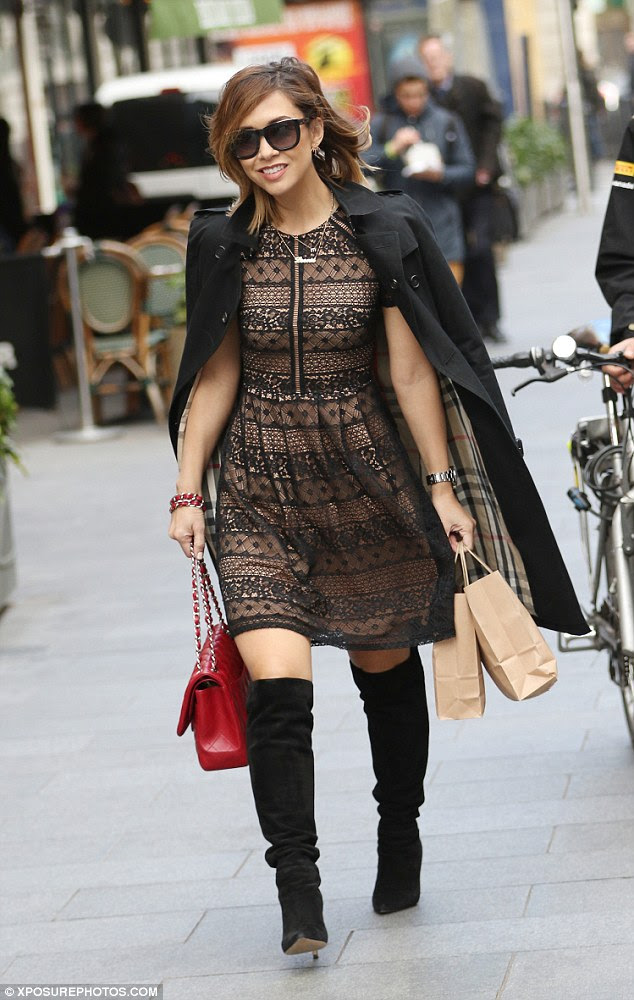 Style queen: The media personality rocked the panelled skater dress with a pair of black knee-high heeled boots, revealing a glimpse of thigh