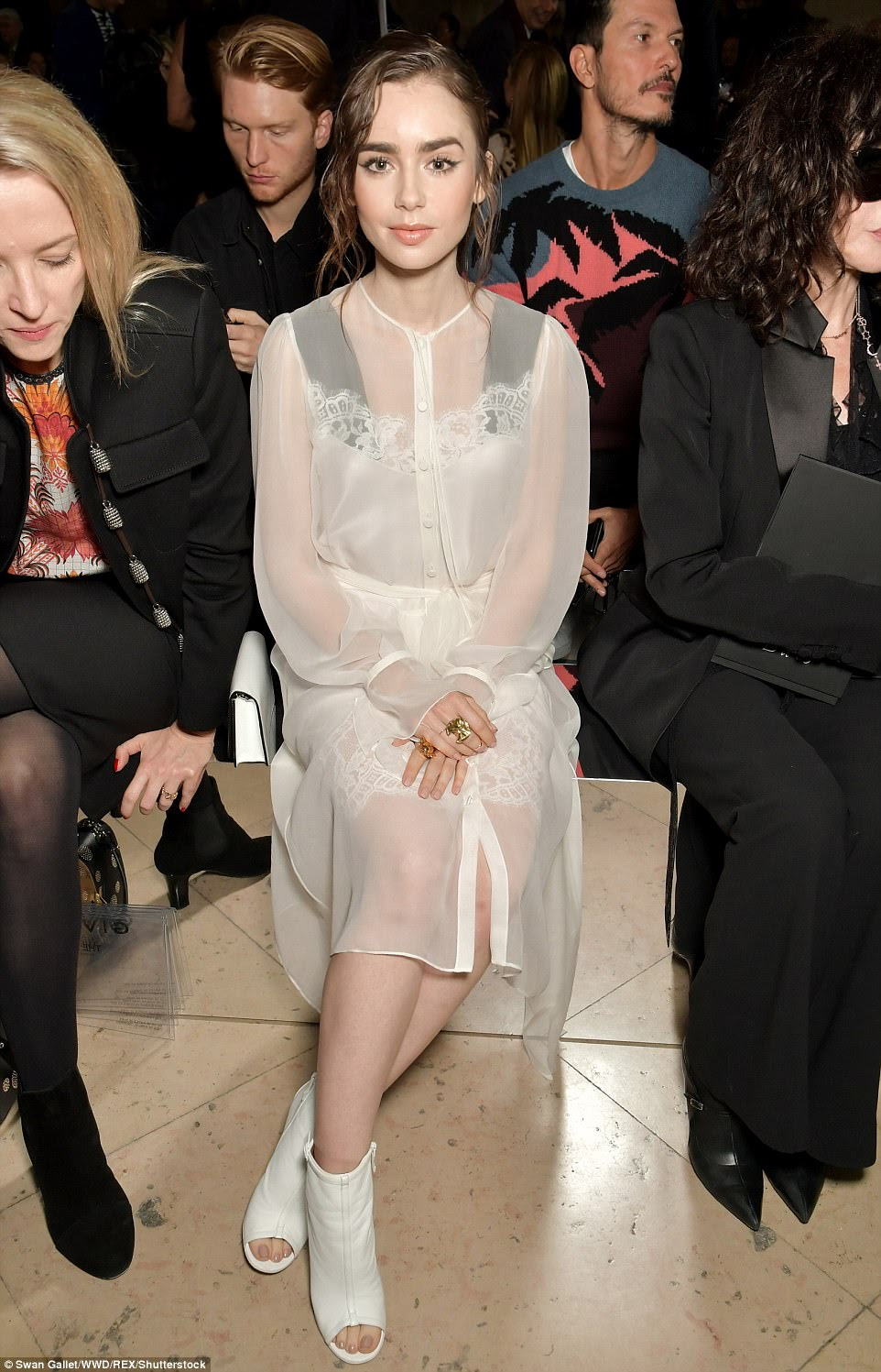 Underwear as outerwear: Model Lily Collins meanwhile proved her flair for high-fashion in a Victoriana-inspired white chiffon shirt dress, layered atop a delicate lace silk slip