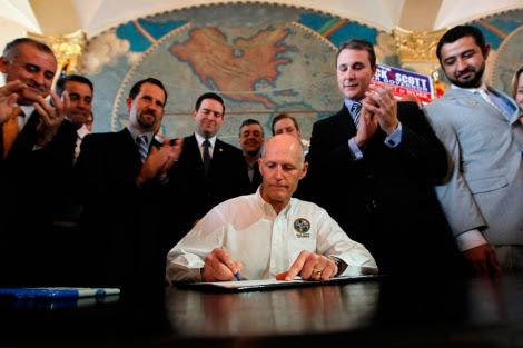 Scott firma entre aplausos la ley. | Afp