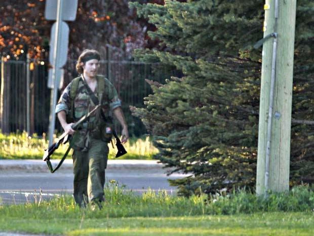 Homem fortemente armado, que a polícia identificou como Justin Bourque, anda por uma rua de Moncton nesta quinta-feira (5)  (Foto: AP Photo/The Canadian Press, Moncton Times & Transcript, telegraphjournal.com, Viktor Pivovarov)