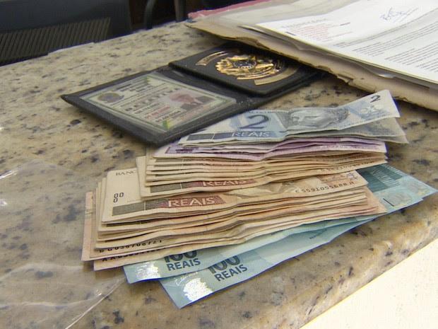 Dinheiro e carteira de detetive apreendidos com o idoso em Tremembé. (Foto: Reprodução/TV Vanguarda)
