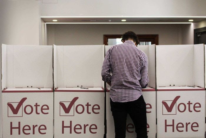 A man fills in his vote at the polling booth