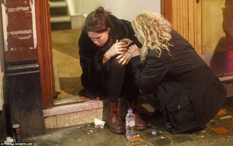 Feeling unwell: A young woman looks poorly and has a bottle of water at her feet while being comforted by another woman in a Soho doorway