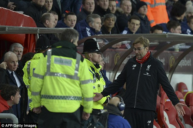 Jurgen Klopp (right) gestures as a heated row between both team's staff members  takes place on Wednesday