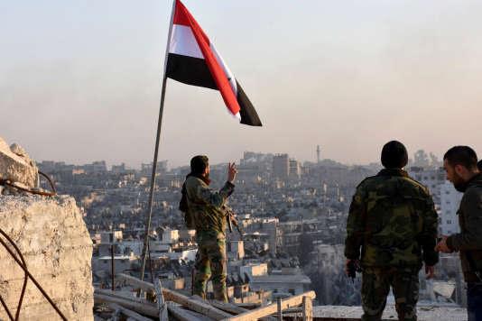 Un soldat du gouvernement syrien fait le V de la victoire sous le drapeau national, à Alep, le 28 novembre 2016 (image fournie par Sana, l'agence de presse officielle de la Syrie)