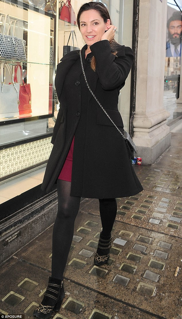 Kelly Brook flashes a glimpse of red skirt