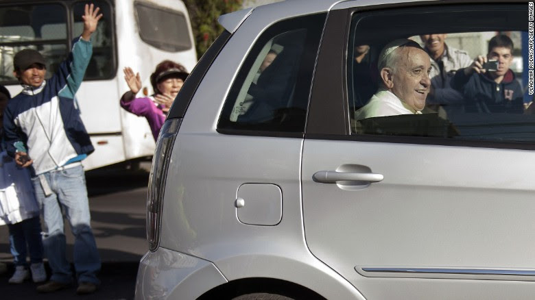 People wave as Pope Francis leaves the Apostolic Nunciature in Quito, Ecuador, on July 6.