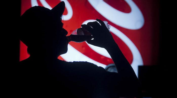 Hombre tomando Coca-Cola.