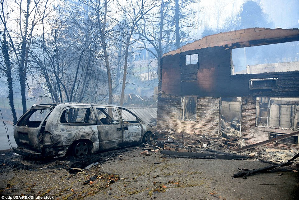 The mayor of Gatlinburg said Tuesday that half of the city was impacted by the blaze, but the downtown area is intact. Above a home and car is destroyed from the fire on Monday