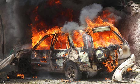 A car goes up in flames near the scene of a blast in Mogadishu, Somalia on April 14, 2013. Despite claims by the corporate media that the country is stable, the war rages on. by Pan-African News Wire File Photos