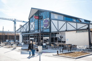 The new Dallas Farmers Market in downtown offers local produce, restaurants, a brewery, and outlets for artisanal food vendors. The second phase of the market will include residential units and additional retail space. (© Hall Group)
