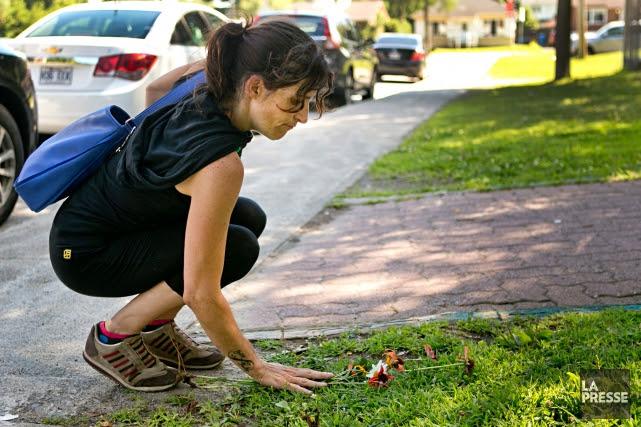 Une femme dépose des fleurs au pied de... (PHOTO DAVID BOILY, ARCHIVES LA PRESSE)