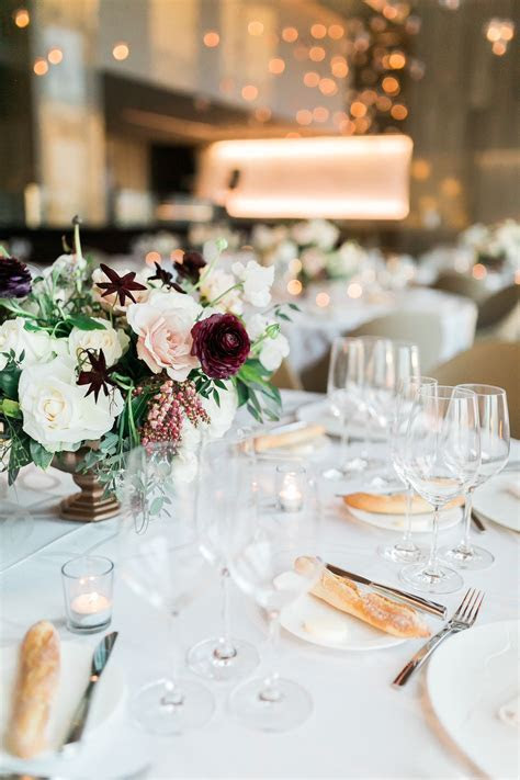 Ivory, blush and burgundy centerpiece in a gold vase with