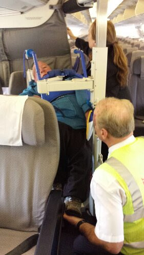 image showing John transferring to his seat in the plane using the eagle lifter with 2 staff assisting.