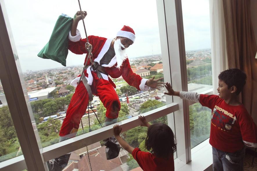 Em comemoração à chegada do Natal, funcionário de um hotel de Surabaya, na Indonésia, limpa as janelas do prédio vestido de Papai Noel - e faz a alegria da criançada