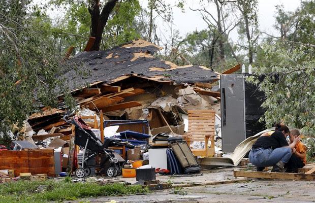 Roshonda Athrom conforta o filho Charles, de 7 anos, em frente à casa destruída na região de Van, no Texas, nesta segunda (11) (Foto: Mike Stone/Reuters)