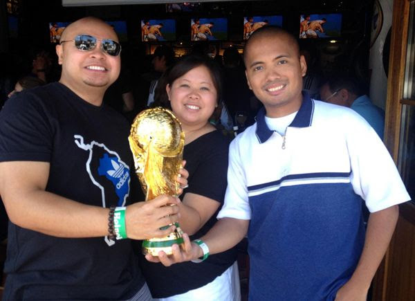 Two of my friends and I pose with the World Cup trophy replica at the Legends sports bar in Long Beach, CA...on July 13, 2014.