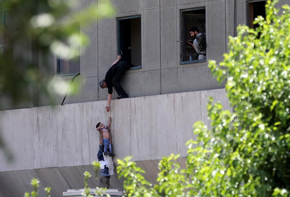 Criança é retirada pela janela durante ataque ao Parlamento do Irã, em Teerã, nesta quarta-feira (7)  (Foto: Omid Vahabzadeh/Tima via Reuters)