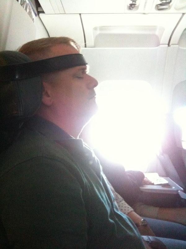 hombre con correa en la frente para dormir en el avion