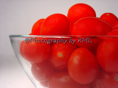 a glass bowl filled with red cherry tomatoes