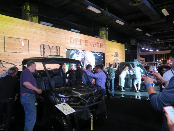 Dealers gather around the Can-Am Defender display in the showroom after the global reveal in Nashville, TN.