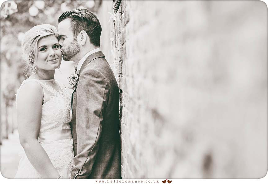 Artistic, quirky photo of Bride and groom by wall - www.helloromance.co.uk