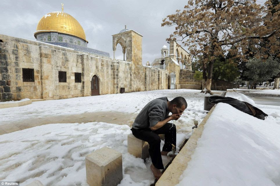 Devotion: Amid the snow and icy temperatures, a Palestinian worshipper gets ready to pray in front of the Dome of the Rock in the compound known to Muslims as Noble Sanctuary and to Jews as Temple Mount, in Jerusalem's Old City