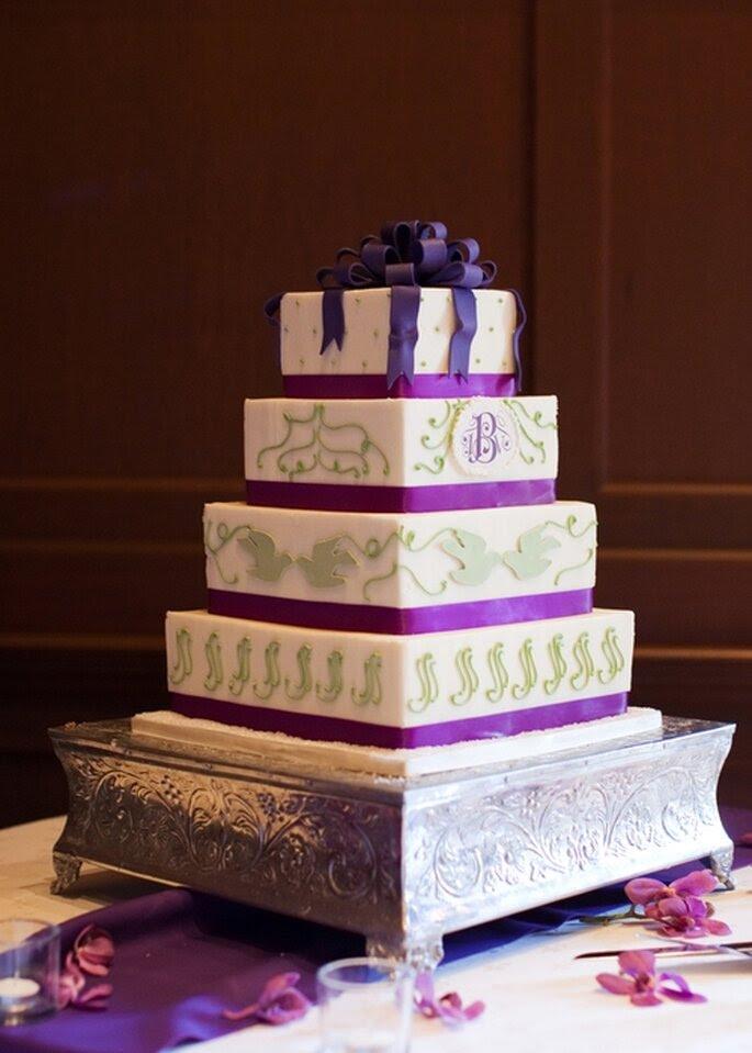 Pastel de boda morado, cuadrado a 4 niveles, adornado con moño y figurillas