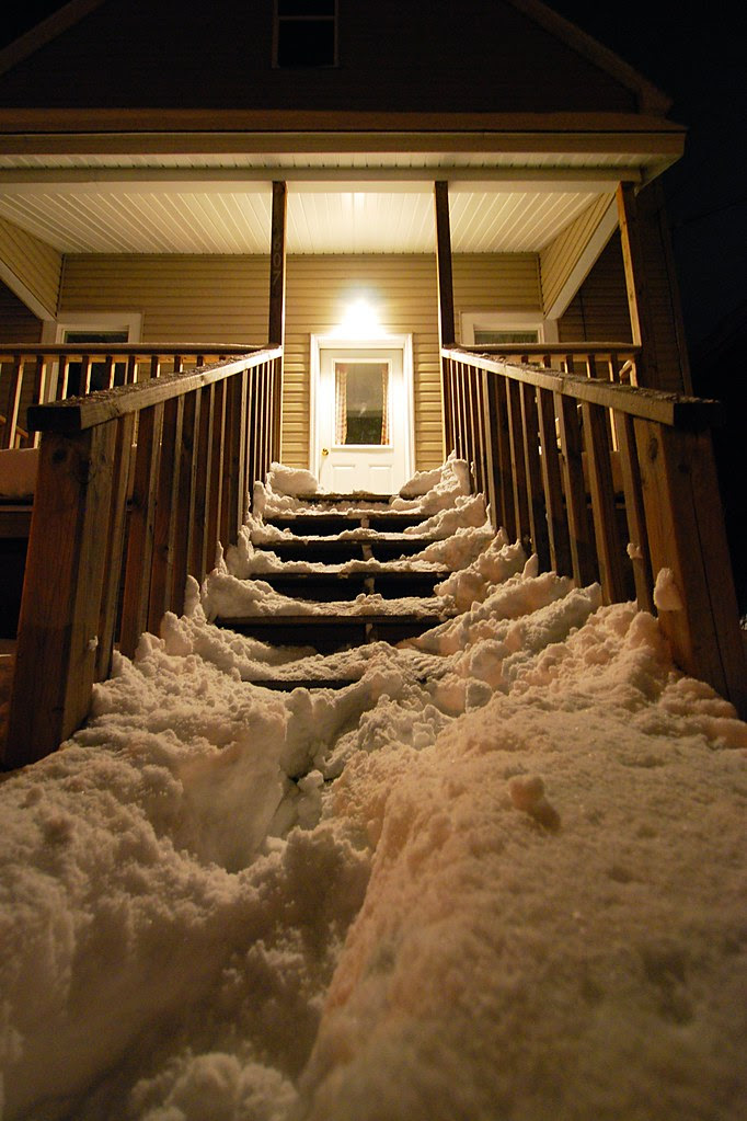 Heavily snow-covered steps leading up to a snowy house, at night.
