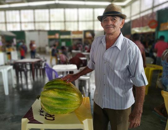 Agricultor ao lado de 'abóbora gigante' exposta na feira livre da cidade | Foto: Notícias de Santaluz