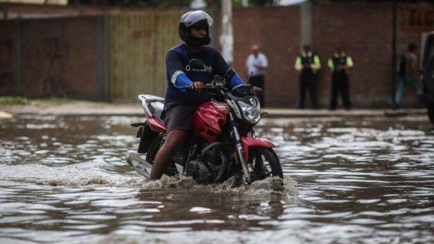 Un motociclista recorriendo una calle de Sullana, en la región Piura, inundada a fines de febrero.