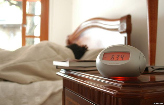 Person in bed, alarm clock on table