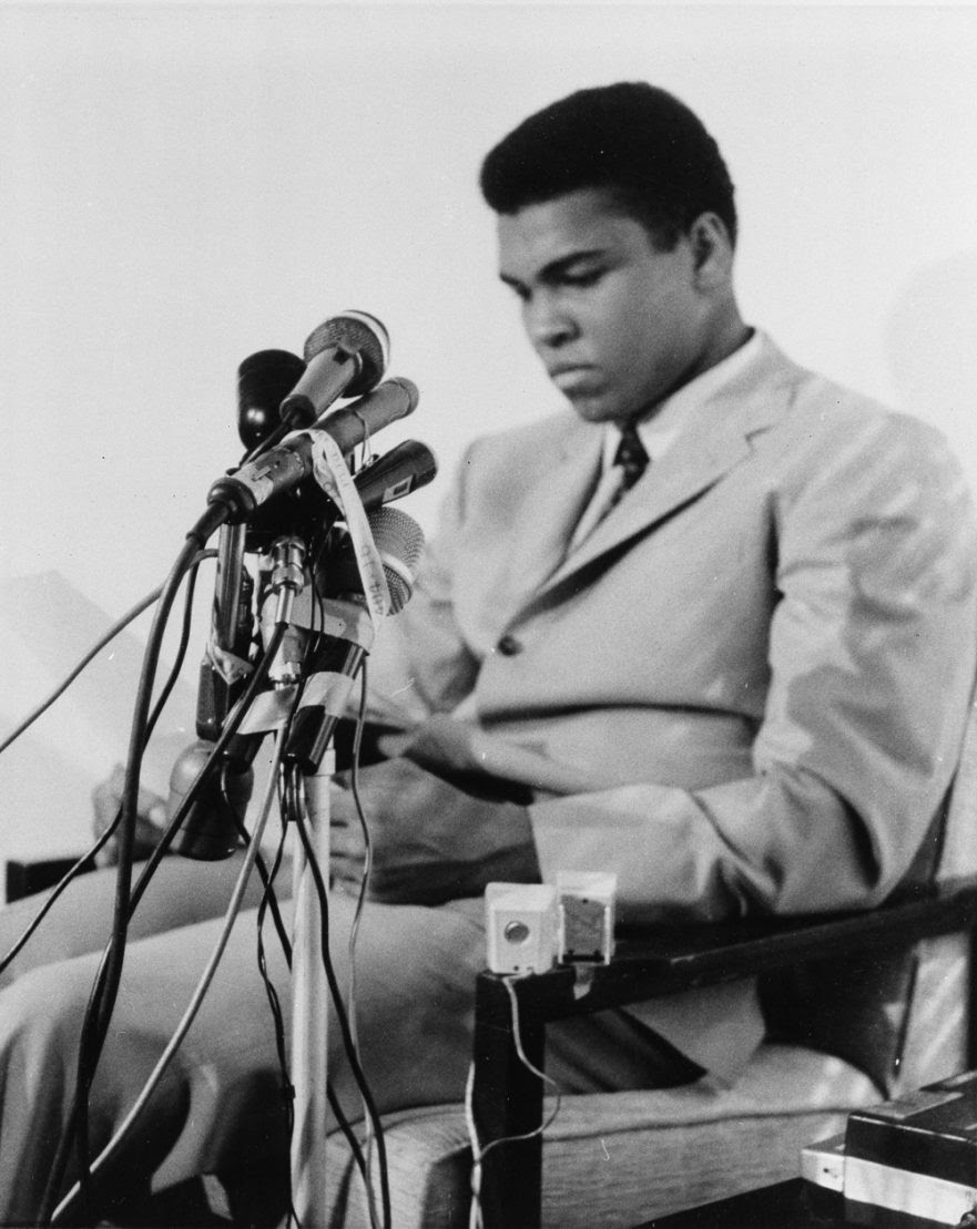 "Muhammad Ali is seen at a news conference in Louisville, Kentucky, April 20, 1967, to say he will not accept miltary service of any nature when he is called for induction In Houston on April 28.  He said ""I ain't got no quarrel with them Viet Cong,"" and that the real enemy of his people ""is right here"" and not in Vietnam or anywhere else.  (AP Photo)"