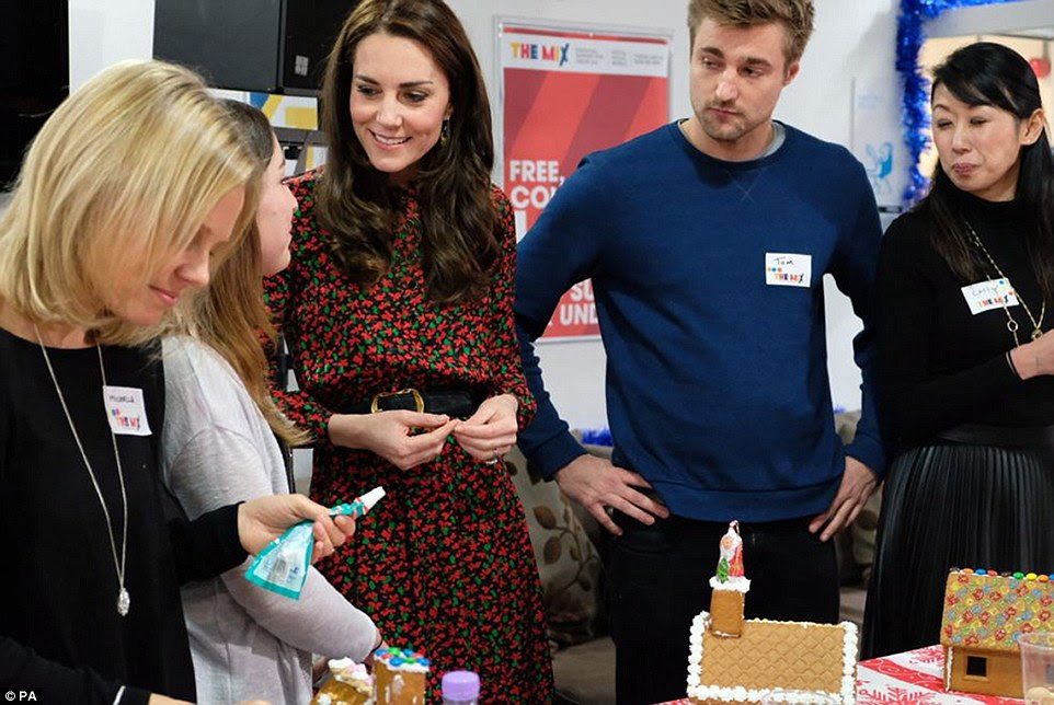 Kate chats to volunteers as they get into the Christmas mood by icing gingerbread houses