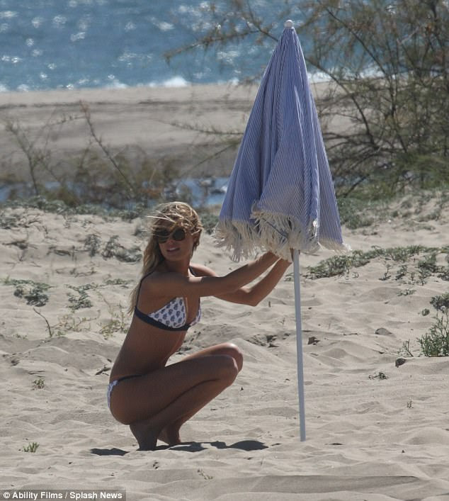 Having trouble? Stripping off her shorts, the caramel-haired beauty then made sure she didn't get too much sun as she grappled with an umbrella to get some shade