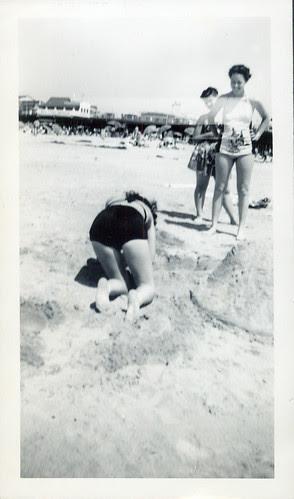 At the beach, Carlelita sifts sand.