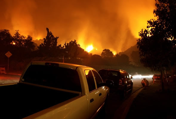 Cars along wildfire evacuation route. Wildfire in the background.