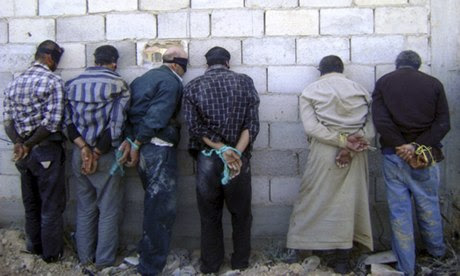 Detained Syrian men, blindfolded and handcuffed, in Qusair, near Homs