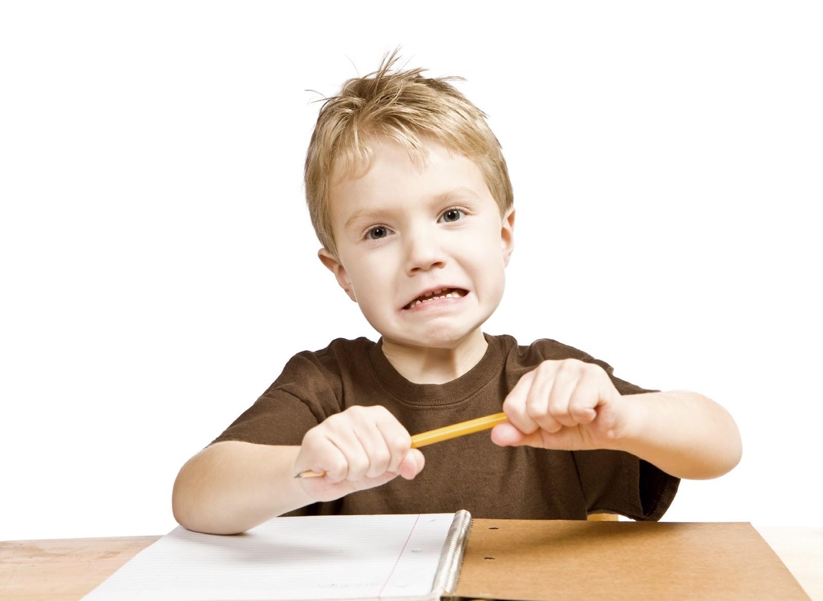 FOTO: um menino com um lápis na mão, como quem tenta quebrá-lo de nervoso